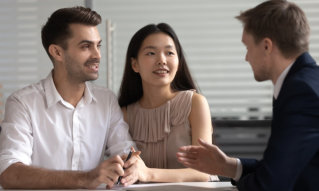 Manager consulting happy diverse young couple about deal