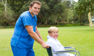 nurse pushing senior patient on wheelchair outdoors