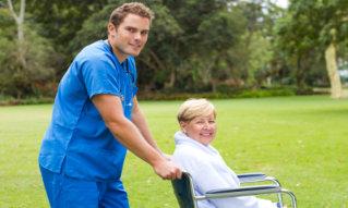 nurse pushing senior patient on wheelchair outdoors