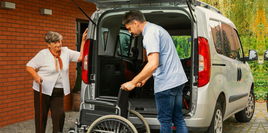 man assisting senior woman on a wheelchair