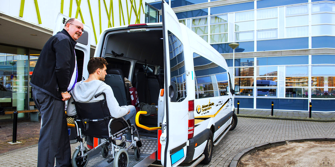 man helping disabled man in wheelchair to ride the van