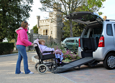 young woman helping her disabled senior woman by assisting her in a van